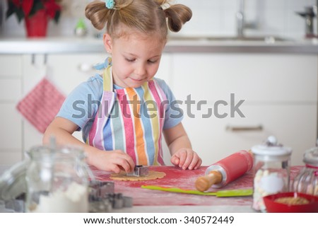 Pretty little girl baking Christmas cookies at home