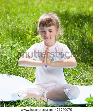 Pretty little girl doing exercises in the summer park