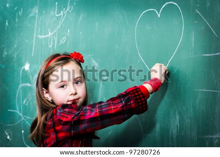 Pretty little girl drawing heart on blackboard - stock photo