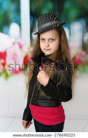 Pretty little girl dressed in black and red with sunglasses in hand and hat on her head with long hair - children beauty and fashion concept - stock photo