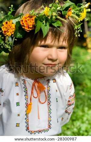 Pretty little girl dressed in Ukrainian folk costume with focused look - stock photo