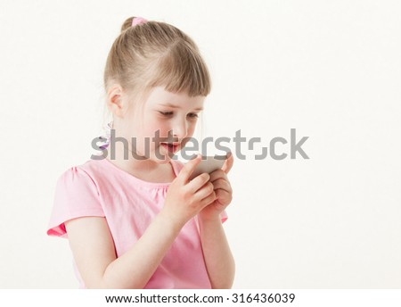 Pretty little girl examining a card, white background - stock photo