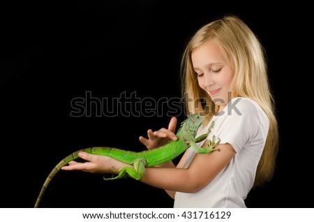 pretty little girl fase and green iguana beautiful portrait - stock photo