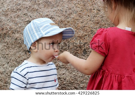 Pretty little girl feeding a younger brother with an ice-cream in the park, summer outdoor portrait - stock photo