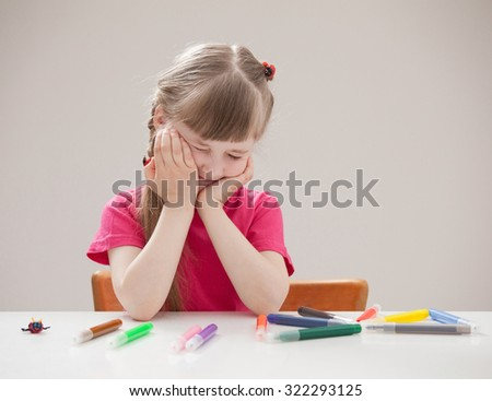 Pretty little girl grimacing and sitting at the table - stock photo