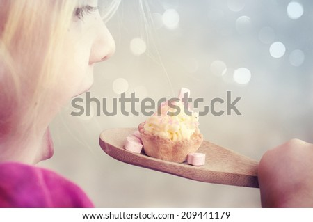 Pretty little girl having fun while eating a delicious birthday cupcake  - stock photo