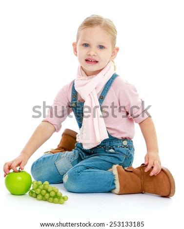 Pretty little girl holding a green apple. Isolated on white background.