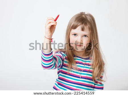 Pretty little girl holding a red felt-tip pen and drawing something, white background - stock photo