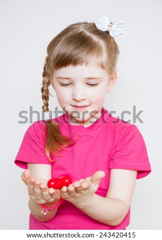 Pretty little girl holding a red heart, white background - stock photo