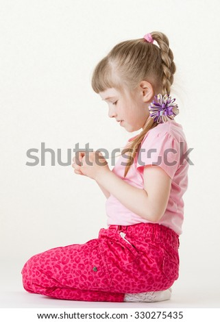 Pretty little girl holding and examining something, white background - stock photo