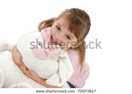 Pretty little girl hugging big white rabbit isolated on white.