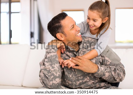 pretty little girl hugging her military father - stock photo