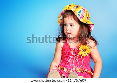 Pretty little girl in a floral hat and dress over grey background.