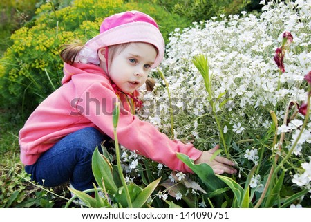 Pretty Little Girl in a Garden with White Flowers - stock photo