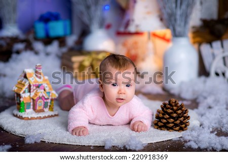 pretty little girl in a New Year's suit near a Christmas tree among snow. blue accent decor - stock photo