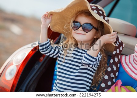 Pretty little girl in a striped dress and hat relaxing on the beach near sea, summer, vacation, travel concept. smiling cute little girl on beach vacation. Baby girl in hat and sun glasses on beach - stock photo