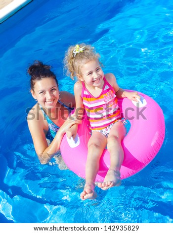 Pretty little girl in an pink life preserver with her mother in swimming pool outdoors. Vertical view. - stock photo