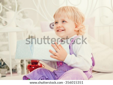 pretty little girl in bed with gifts for Christmas - stock photo