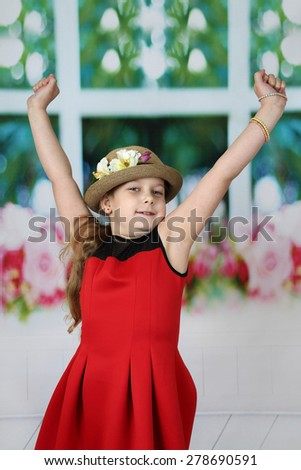 Pretty little girl in hat stretches herself raising hands up in the morning - children beauty and fashion concept - stock photo