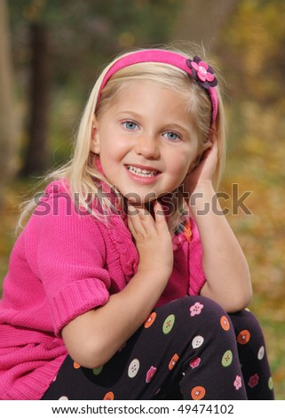 pretty little girl in pink sweater sitting outside - stock photo