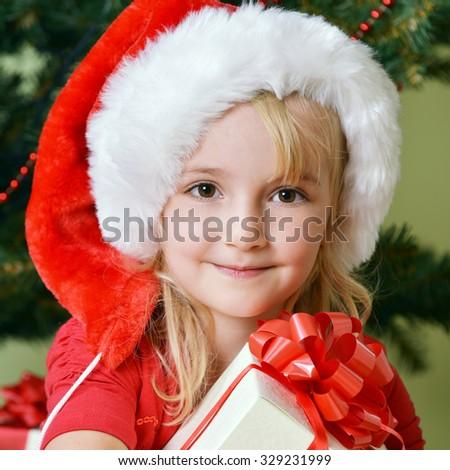 Pretty little girl  in santa cap near Christmas tree - stock photo