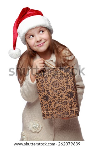 Pretty little girl in Santa's hat holding her Christmas present, isolated on white background - stock photo