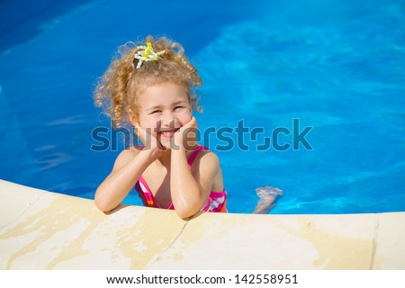 Pretty little girl in swimming pool outdoors - stock photo