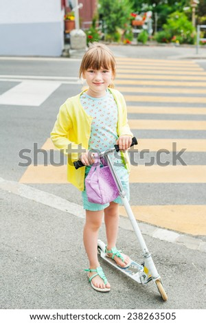 Pretty little girl is going to cross the road alone - stock photo