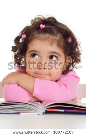 Pretty little girl is reading sitting at the table - stock photo