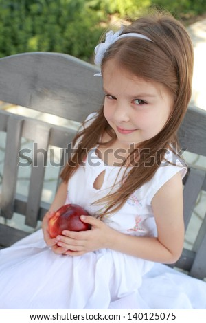 Pretty little girl is sitting in a park on a bench and holding a red apple