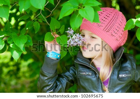 Pretty little girl is smelling flowers in park - stock photo