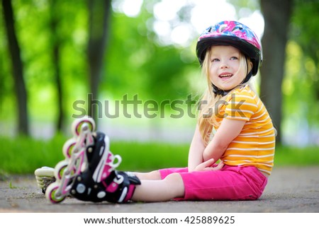 Pretty little girl learning to roller skate outdoors on beautiful summer day - stock photo
