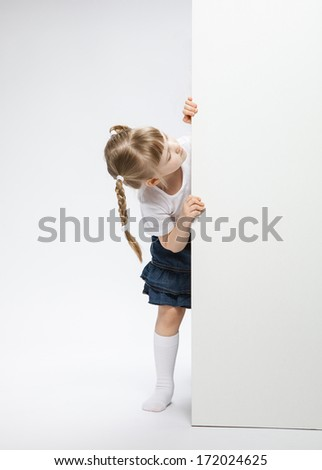 Pretty little girl looking  out of the door, neutral background - stock photo