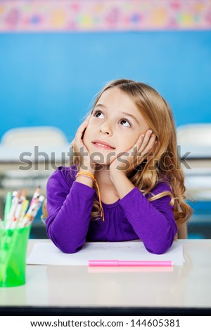 Pretty little girl looking up while sitting with head in hands in drawing class - stock photo