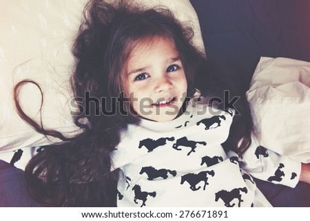 pretty little girl lying in bed - stock photo