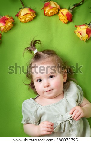 pretty little girl lying on green blanket with yellow roses - stock photo