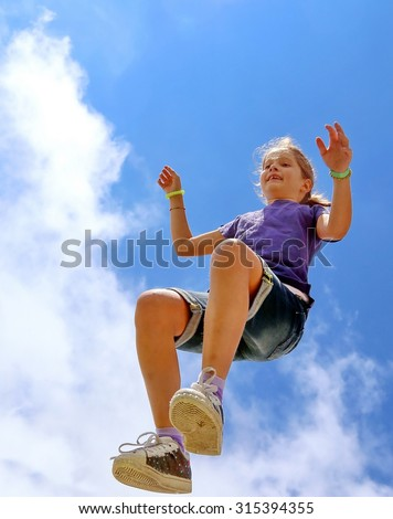pretty little girl makes a big jump and blue sky in summer