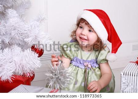 pretty little girl  near the new year tree - stock photo