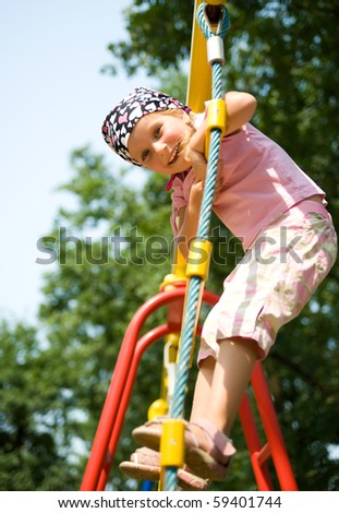 Pretty little girl on outdoor playground equipment - stock photo