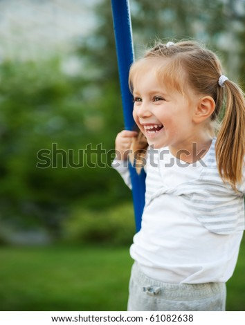 Pretty little girl on outdoor seesaw - stock photo