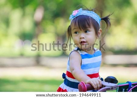 Pretty little girl on the bicycle in park - stock photo