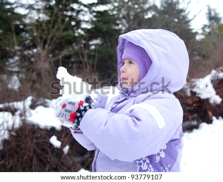 pretty little girl outdoors playing with snowball, winter - stock photo