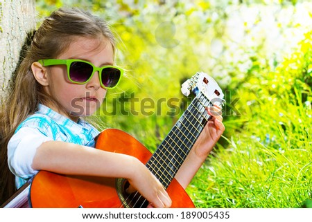 Pretty little girl playing a guitar. Spring time - stock photo