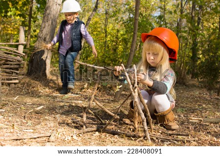 Pretty little girl playing at being a builder squatting on the ground in woodland building a wooden framework in her hardhat as a little boy fetches twigs for her