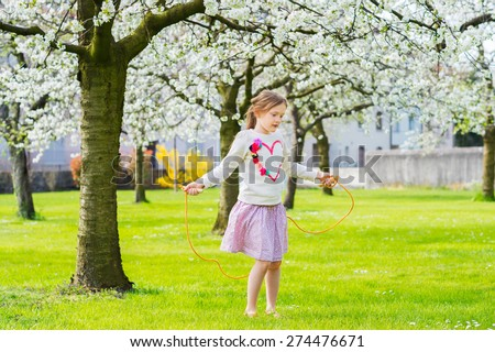 Pretty little girl playing in a spring garden on a nice sunny day, jumping with skipping rope, wearing sweatshirt with a heart and pink skirt - stock photo