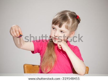 Pretty little girl playing with a plasticine toy, neutral background - stock photo