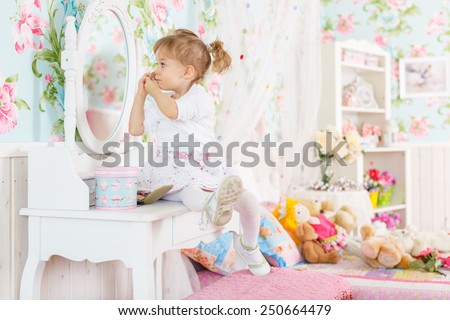 Pretty little girl playing with cosmetics near dressing table in the room. 2 year old. - stock photo
