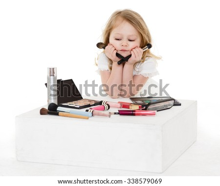 Pretty little girl playing with cosmetics on a white background. 3 year old. - stock photo