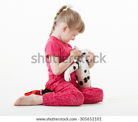 Pretty little girl playing with plush toy, white background