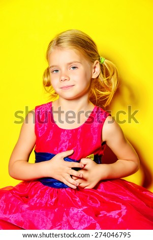 Pretty little girl posing in bright pink dress over yellow background. Fashion shot. Childhood. - stock photo